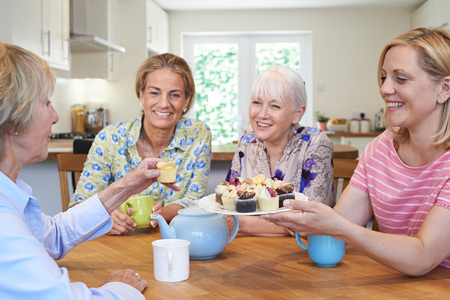 Group Of Different Aged Female Friends Meeting At Home