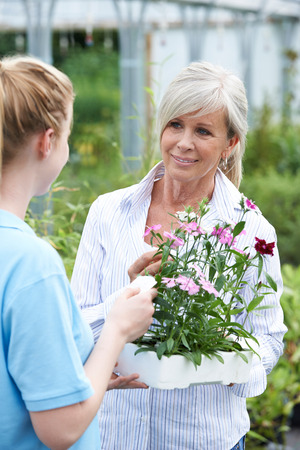 Staff Giving Plant Advice To Female Customer At Garden Center
