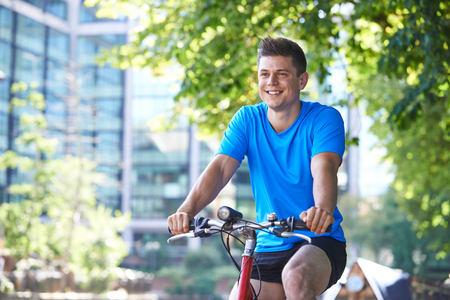 Young Man Cycling Next To River In Urban Setting
