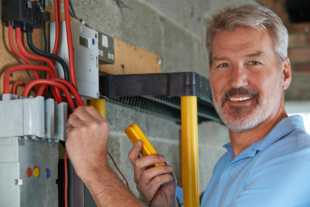 Portrait Of Electrician Standing Next To Fuseboard Banque d'images