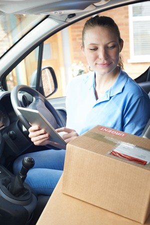 Female Courier In Van Delivering Package To House