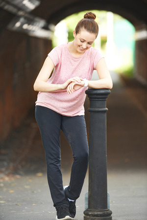 Woman Looking At Activity Tracker Whilst Exercising In Urban Setting