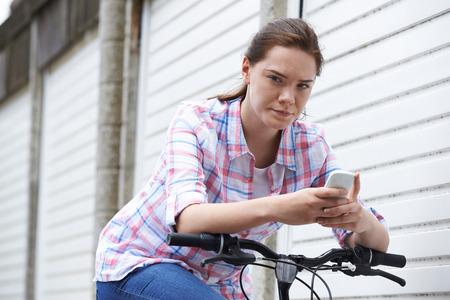 Portrait Of Teenage Girl On Bike Texting Using Mobile Phone