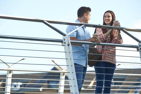 Young Couple Talking On Bridge In Urban Setting Holding Takeaway Coffee