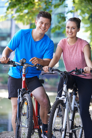 Portrait Of Young Couple Cycling Next To River In Urban Setting