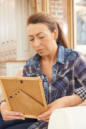 Unhappy Mature Woman Looking At Photograph In Frame Banque d'images