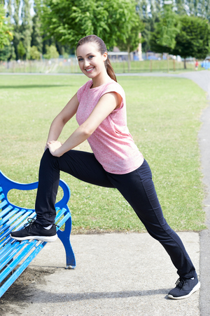 Portrait Of Woman In Fitness Clothing Doing Stretches Using Park Bench