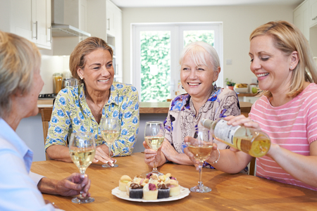 Group Of Different Aged Female Friends Relaxing At Home And Drinking Wine Banque d'images
