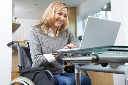 Disabled Woman In Wheelchair Using Laptop At Home Banque d'images