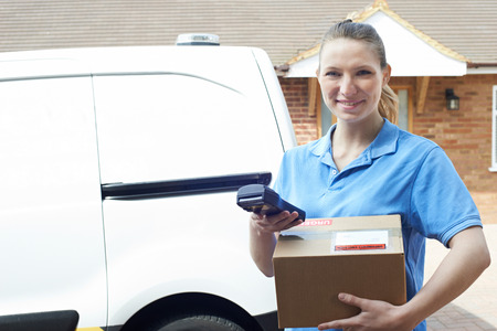 Portrait Of Female Courier With Van Delivering Package To House Banque d'images