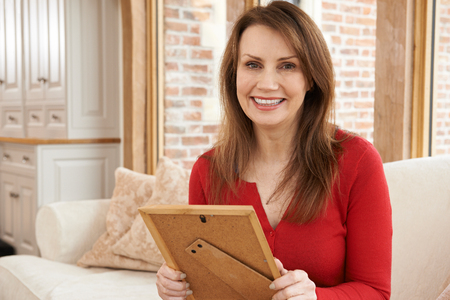 Portrait Of Smiling Mature Woman Looking At Picture Frame At Home