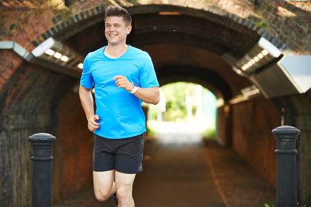 Man Wearing Fitness Tracker Running In Urban Environment