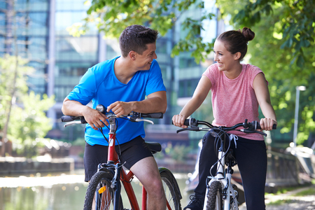 Young Couple Cycling Next To River In Urban Setting Banque d'images