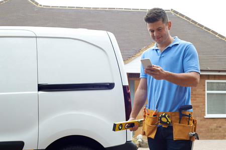 Builder With Van Texting On Mobile Phone Outside House Stok Fotoğraf