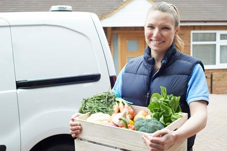 Mujer haciendo entrega a domicilio de caja de vegetales orgánicos Foto de archivo - 86369640