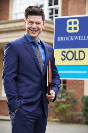 real estate sold: Male Realtor Standing Outside Residential Property With Sold Sign