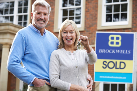 Mature Couple Holding Keys To New Home Standing By Sold Sign