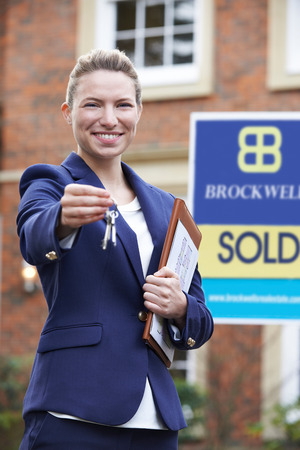 real estate sold: Female Realtor Standing Outside Residential Property Holding Keys