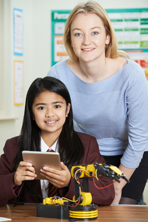 Teacher With Female Pupil In Science Lesson Studying Robotics