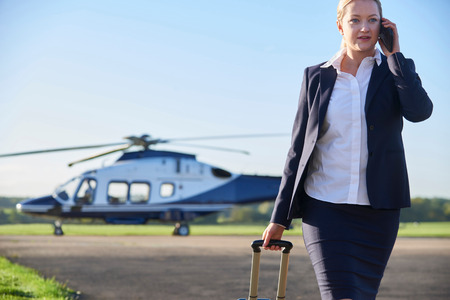 Businesswoman Walking Away From Helicopter Whilst Talking On Mobile Phone Banque d'images