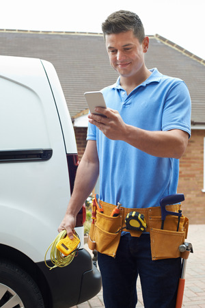 Electrician With Van Sending Text Message On Mobile Phone Outside House