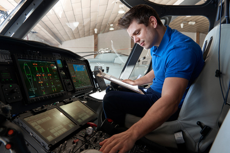 Male Aero Engineer With Clipboard Working In Helicopter Cockpit Stock Photo