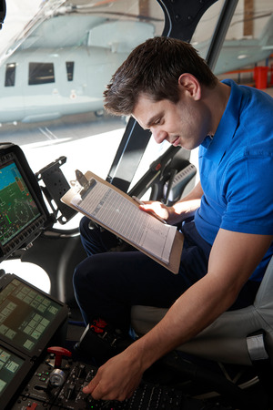 Male Aero Engineer With Clipboard Working In Helicopter Cockpit Banque d'images