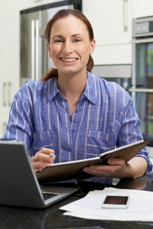 Portrait Of Female Freelance Worker Using Laptop In Kitchen At Home Banque d'images