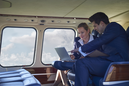 Businessman And Businesswoman Working On Laptop In Helicopter Cabin Banque d'images