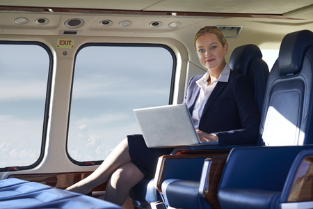 Portrait Of Businesswoman Working On Laptop In Helicopter Cabin During Flight Banque d'images