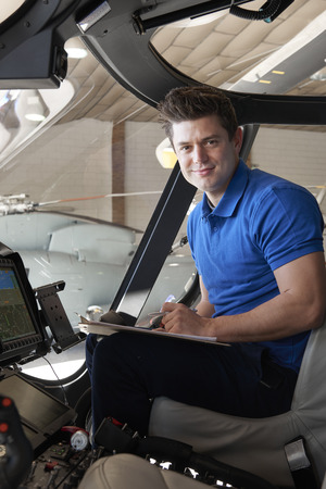 Portrait Of Male Aero Engineer With Clipboard Working In Helicopter Cockpit Banque d'images