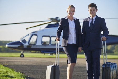 Portrait Of Businesswoman And Businessman Standing In Front Of Helicopter  Banque d'images