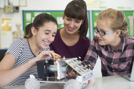 Teacher Talking To Female Pupils Studying Robotics In Science Lesson