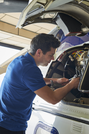 Male Aero Engineer Working On Helicopter In Hangar