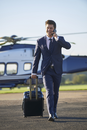 Businessman Walking Away From Helicopter Whilst Talking On Mobile Phone Banque d'images