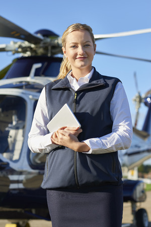 Portrait Of Female Pilot Standing In Front Of Helicopter With Digital Tablet