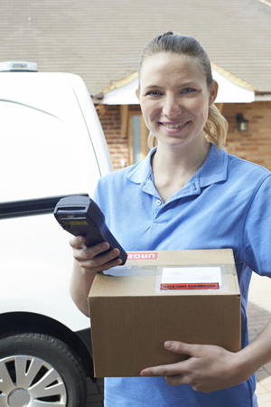 Female Courier Delivering Package To Domestic House Banque d'images