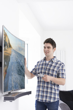Young Man With New Curved Screen Television At Home Banque d'images