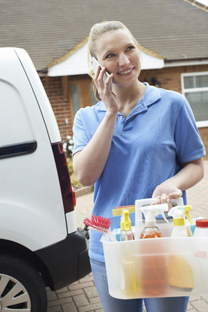 Young Woman Running Mobile Cleaning Business With Van Using Mobile Phone Banque d'images