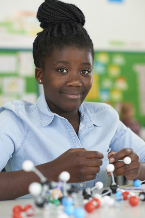 Female Pupil Using Molecular Model Kit In Science Lesson Stock Photo