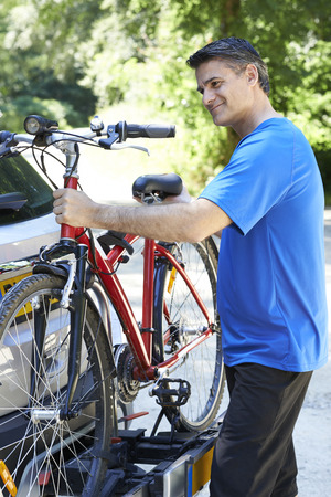 Mature Male Cyclist Taking Mountain Bike From Rack On Car