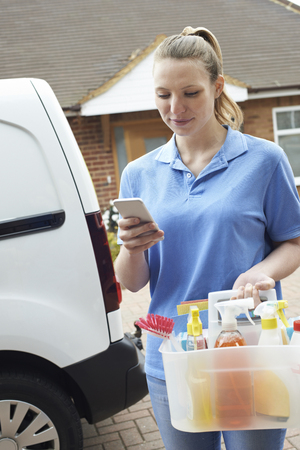Woman Running Mobile Cleaning Business With Van Checking Text Message On Mobile Phone