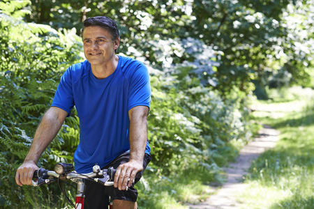 Mature Man Cycling Along Path In Countryside