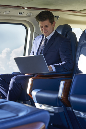 Businessman Working On Laptop In Helicopter Cabin During Flight Banque d'images