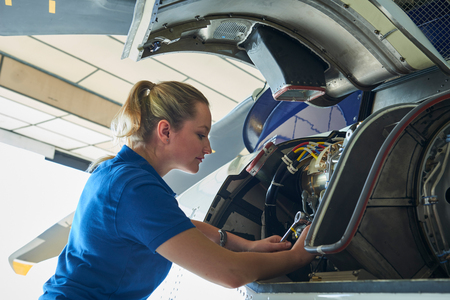 Female Aero Engineer Working On Helicopter In Hangar