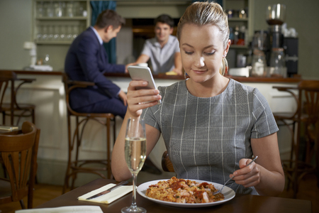 Female  Posting Online Review Of Restaurant Meal Using Mobile Phone