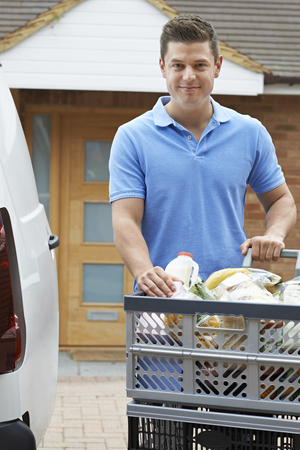 Portrait Of Driver Delivering Online Grocery Order To House