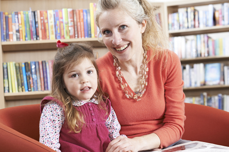 Portrait Of Mother And Daughter Reading Book In Library Banque d'images