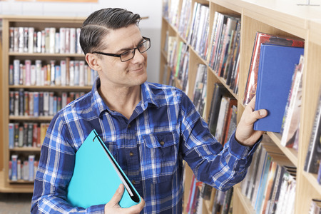 Mature Male Student Taking Book From Shelf In Library