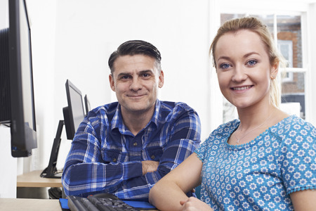 Mature Man Training Young Woman On Computer In Office